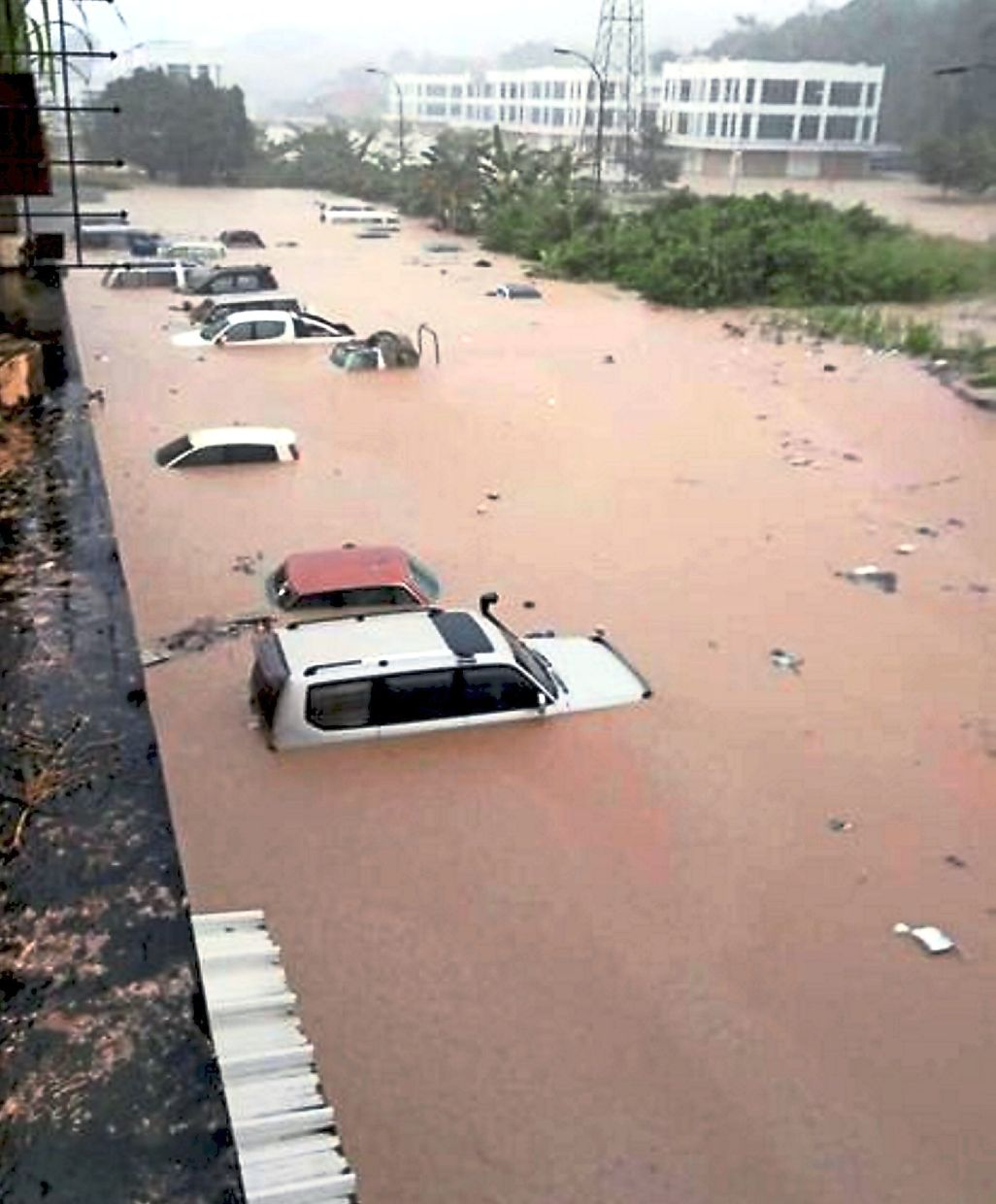 Cars parked in a commercial complex area at Telipok, Kota Kinabalu, partially submerged as water began rising in the early afternoon.