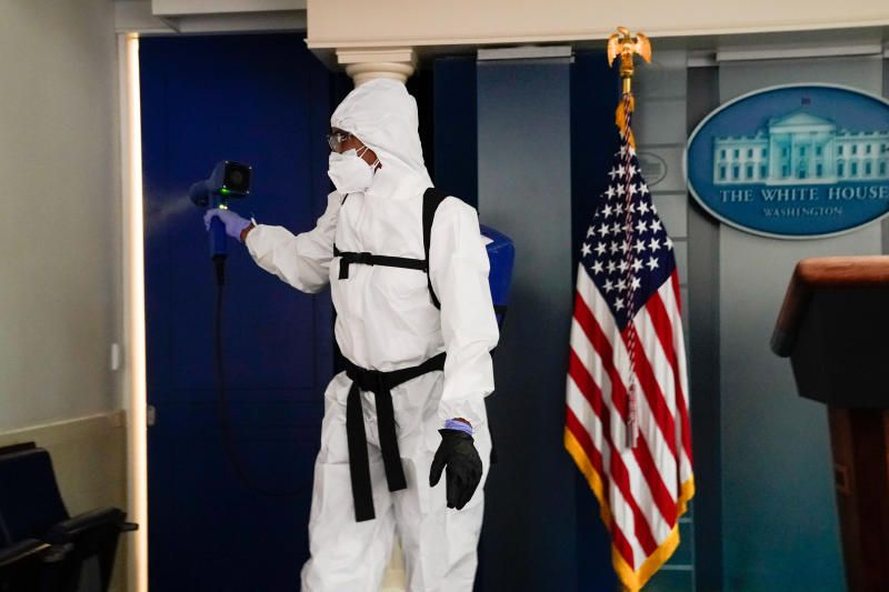 A member of the White House staff cleaning the press briefing room the evening of US President Donald Trump's return from Walter Reed Medical Centre after contracting Covid-19 in Washington. - Reuters