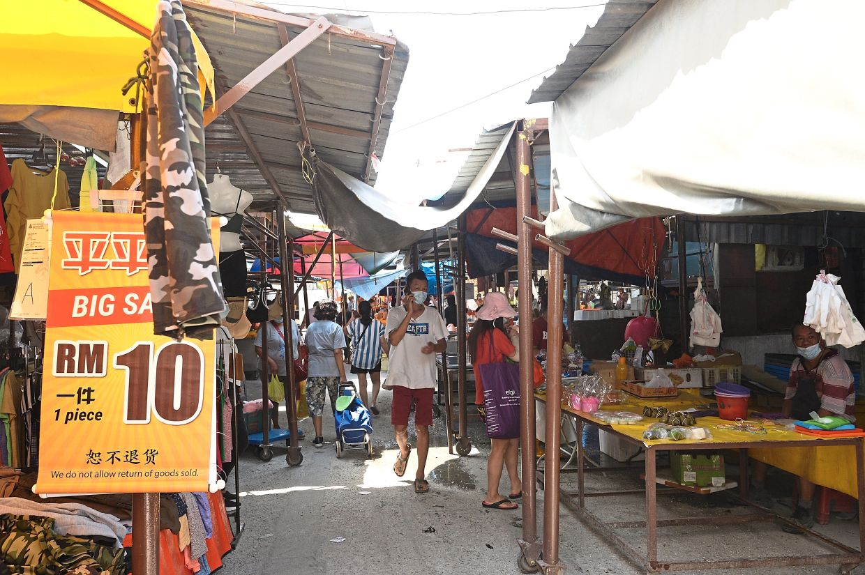 Clothes, vegetables and fresh meat stalls are located next to each other at the open-air market.