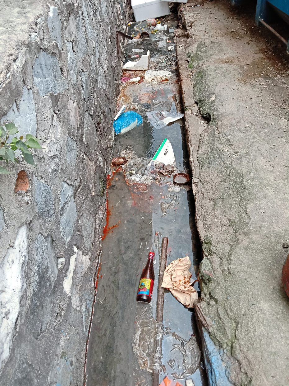 Years of sludge from grease coming from coffeeshops, as well as food waste and rubbish from stalls are what floats in the drains of the Kepong Baru morning market.