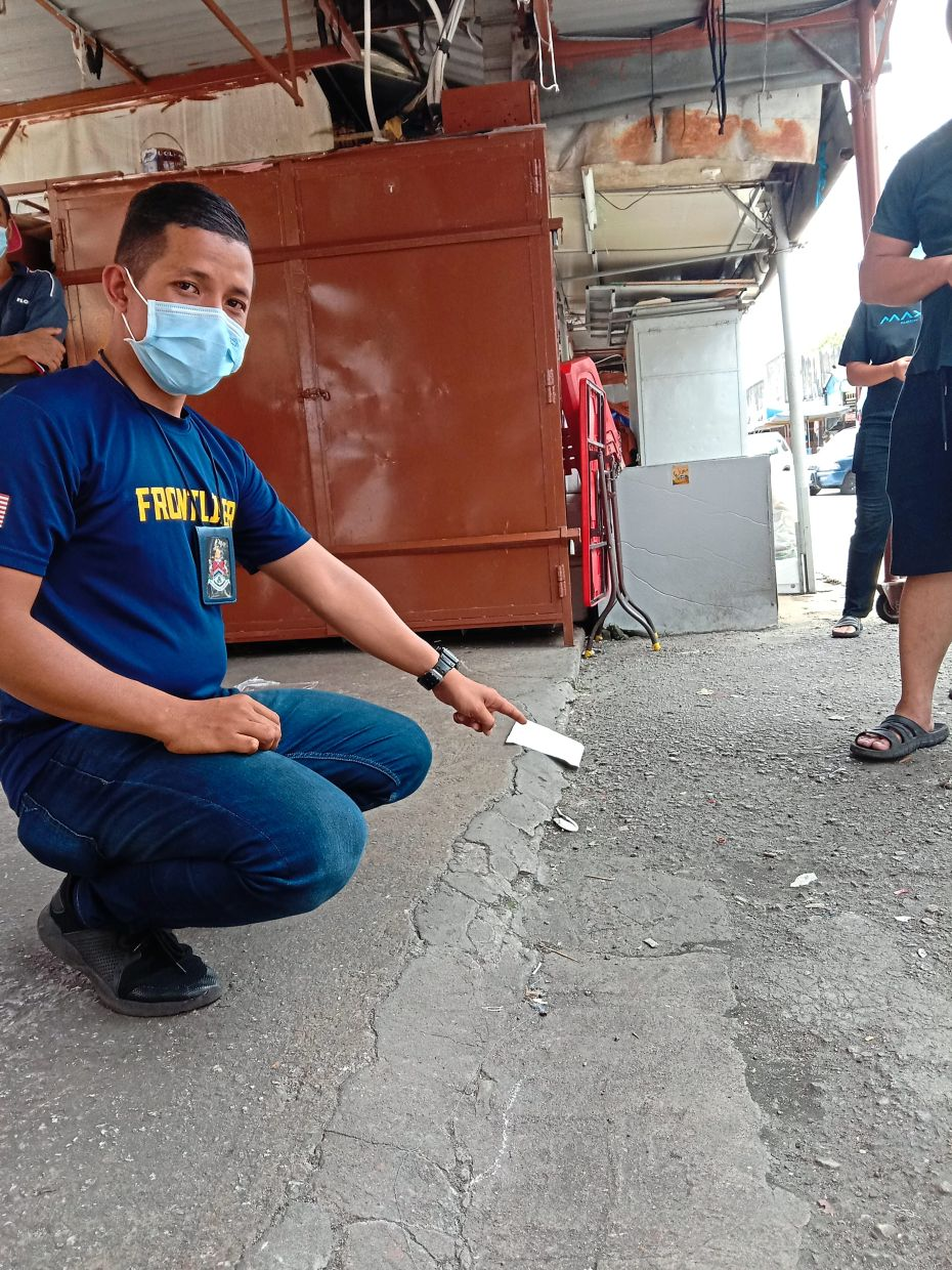 A DBKL licensing officer showing the drain covered with concrete at one of the stalls.