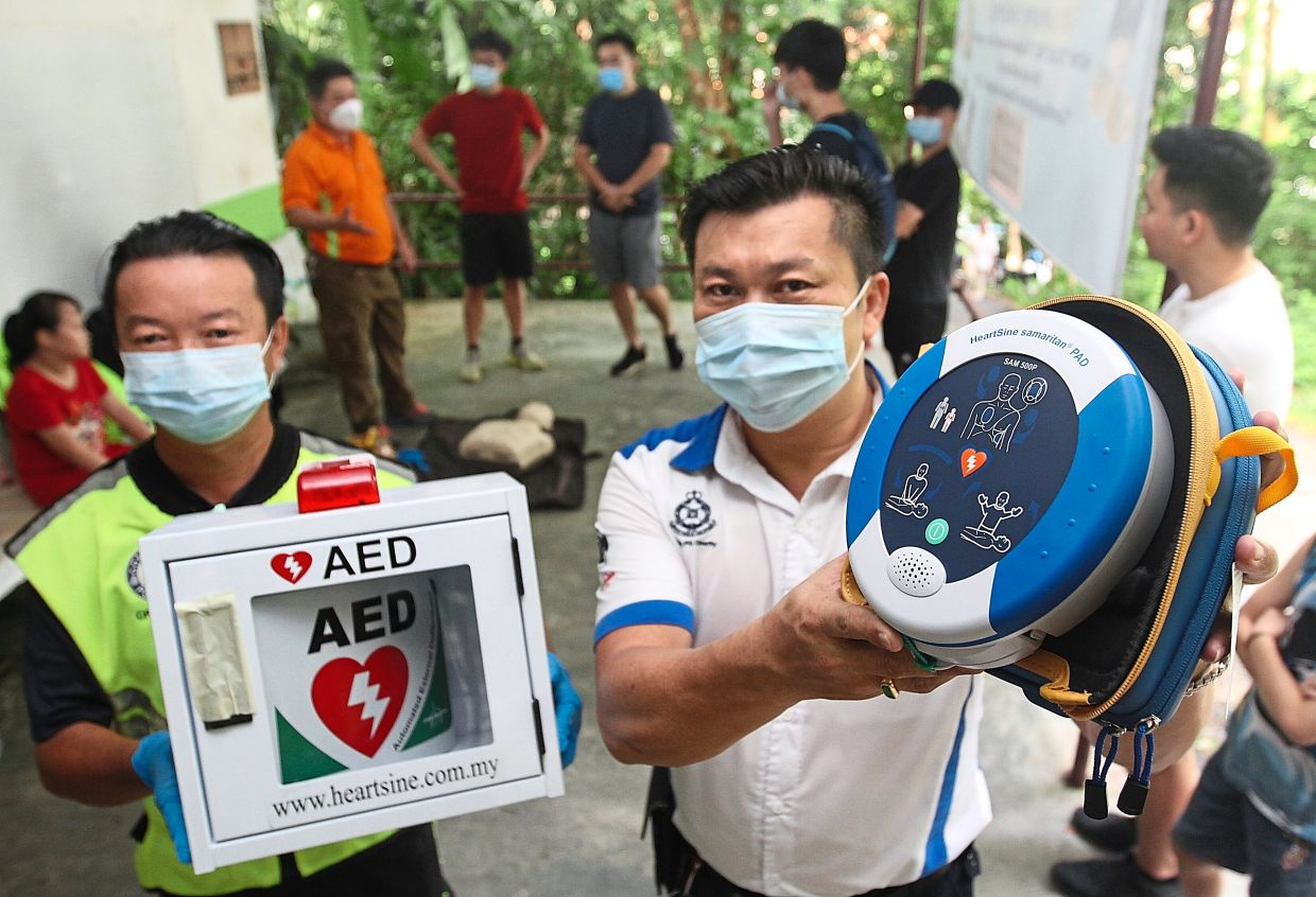 Lim (right) and Penang Community Policing Charity Team member Oon Soon Mooi showing the AED to be installed at the Bukit Jambul hiking trail.