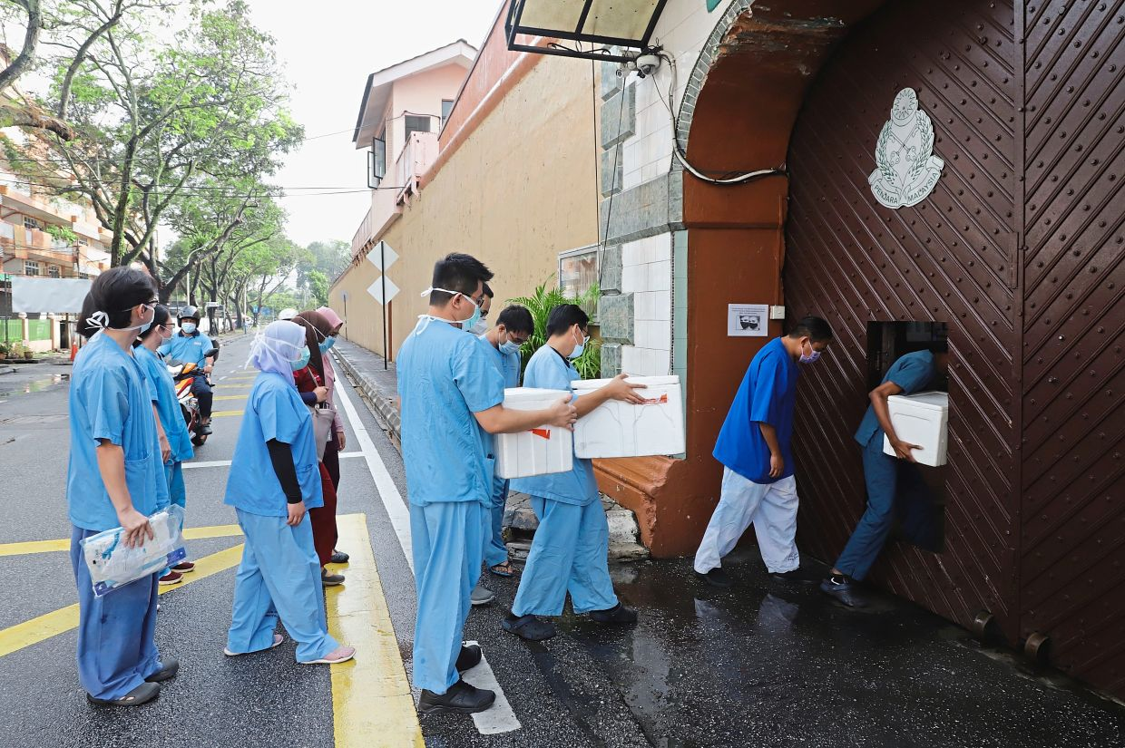 Lockup locked down: State health department personnel entering the Penang Remand Prison to conduct swab tests on more than 2,000 inmates. — LIM BENG TATT/The Star