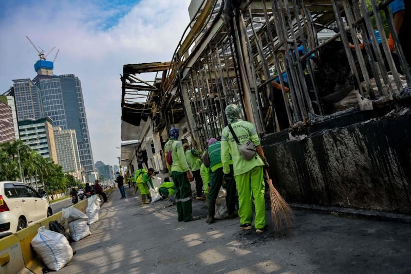 Workers cleaning public facilities that have been destroyed and burnt during a protest that turned into violence during the new controversial law which critics fear will favour investors at the expense of labour rights and the environment in Jakarta on Friday (Oct 9, 2020). - AFP