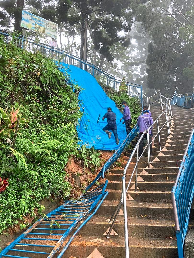 Workers placing tarpaulin sheets over the slope where the boulder had rolled down and damaged the metal railings in Penang Hill.