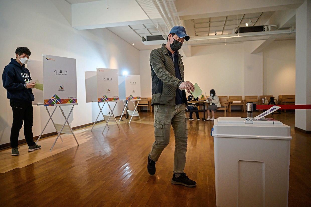 A voter wearing a face mask and gloves amid concerns over the covid-19 novel coronavirus exits a booth to cast a ballot during parliamentary elections at a polling station in Seoul in April.—  AFP