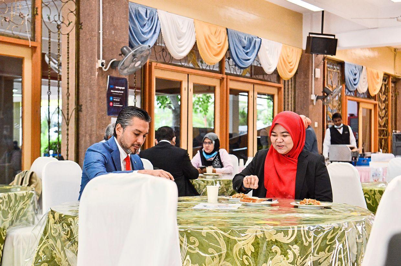Khaliq Mehtab Mohd Ishaq (Bersatu-Bertam) and Nor Hafizah Othman (BN-Permatang Berangan) chatting over a meal during break time.