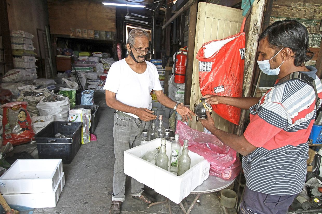 Paramasiwam attending to a visitor bringing bottles to the recycling shop.