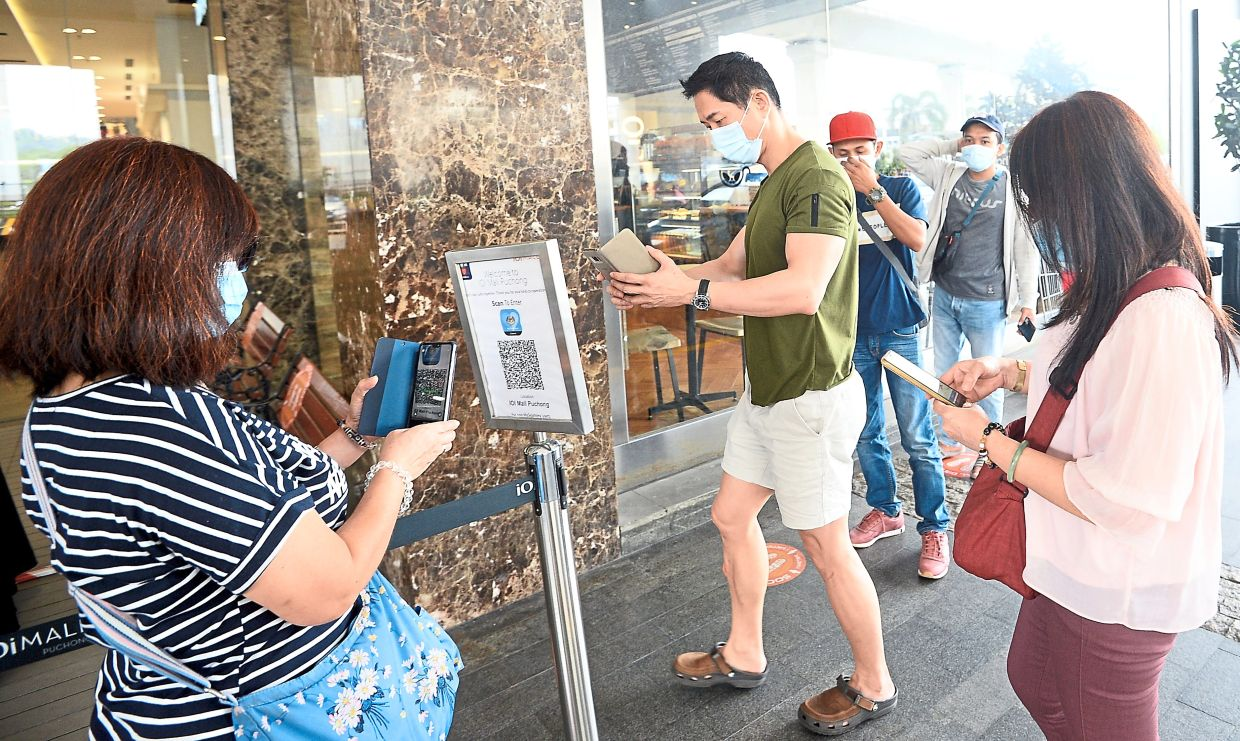 Visitors waiting in an orderly queue to scan the QR code before entering a shop in the Klang Valley.