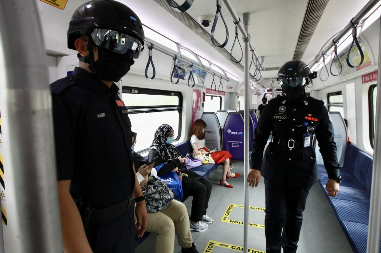 KTMB auxiliary police officers Siti Nabila Isnariah Mohd Jonib (right) and Muhammad Amir Nor Asri, wearing Smart Helmets, making their rounds inside a KTM train at the KL Sentral station. The helmets are made in Malaysia.  NORAFIFI  EHSAN/The Star
