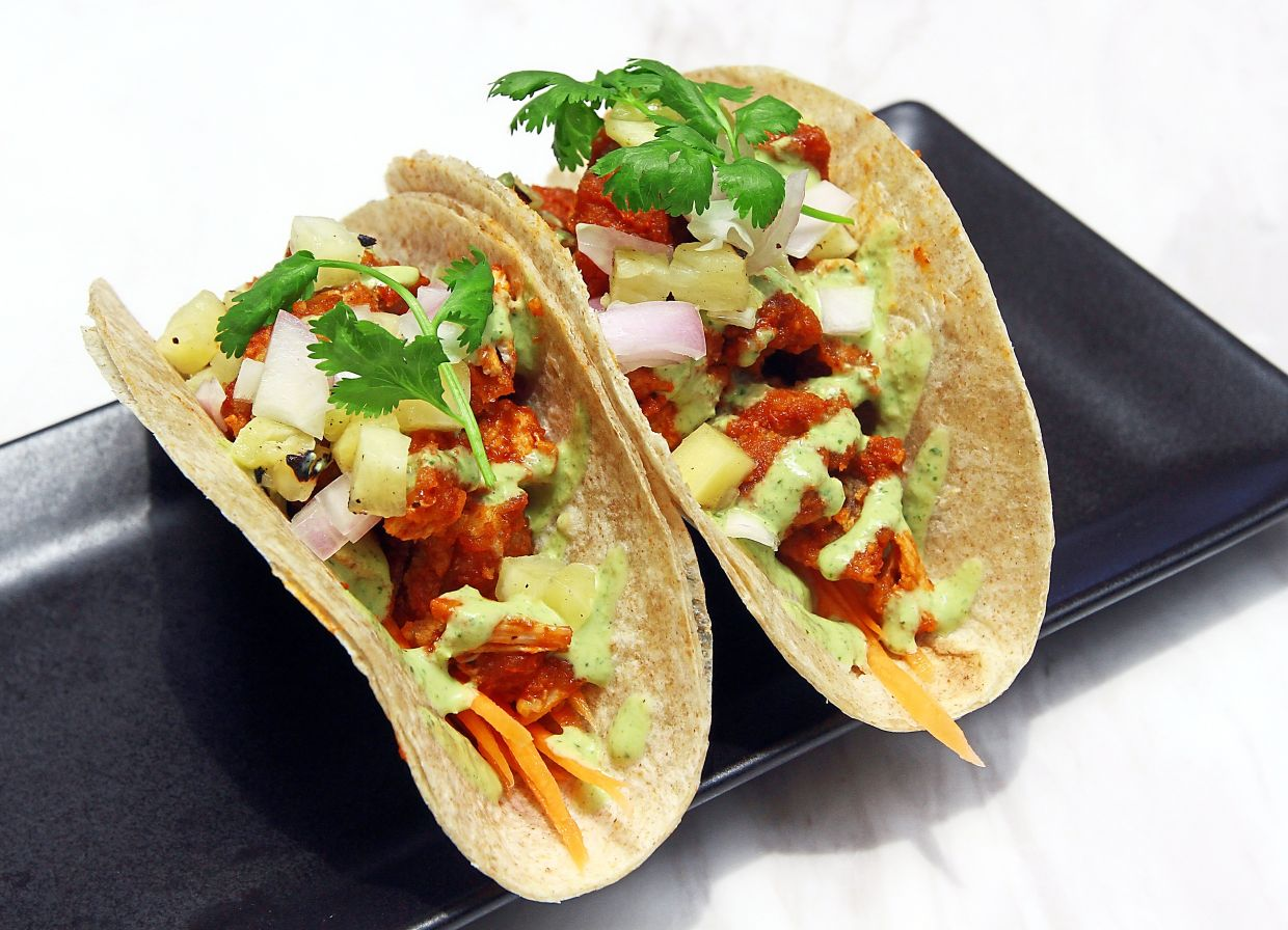 Chicken Tacos Diablo is served with crispy chicken thigh dressed in chipotle BBQ sauce, grilled pineapple, pickled carrot and chimichurri ranch dressing.
