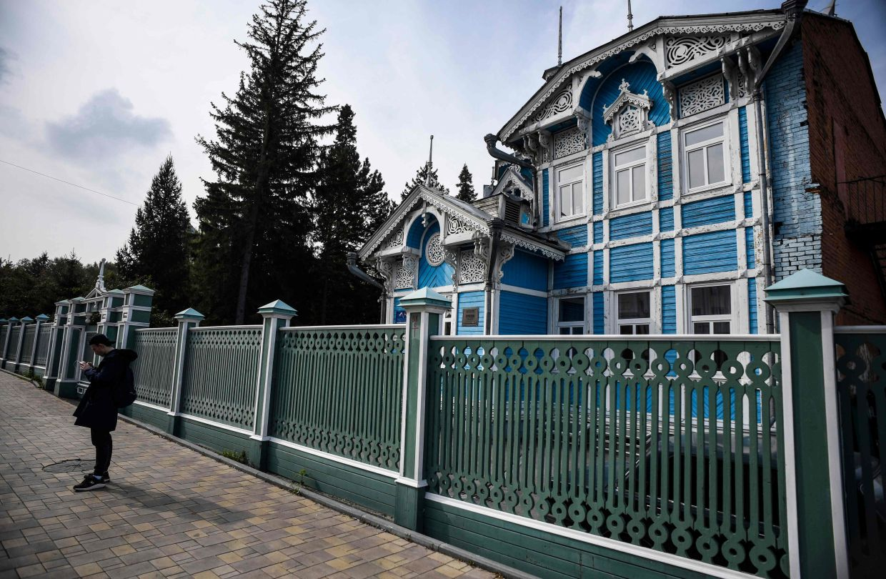 A man stands in front of a house of German- Russian Friendship, a traditional wooden house in the Siberian city of Tomsk. Photo: AFP