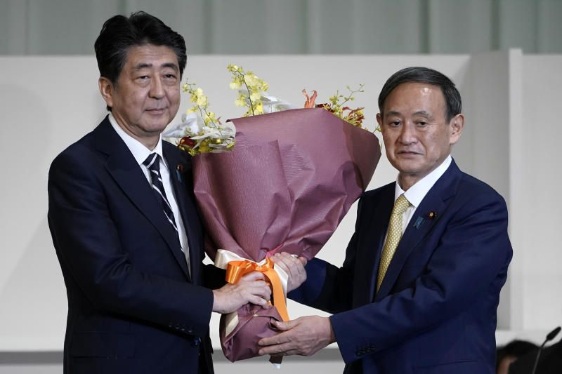 In this Sept 14, 2020, file photo, Japan's then Prime Minister Shinzo Abe, left, receives flowers from then Chief Cabinet Secretary Yoshihide Suga after Suga was elected as new head of Japan's ruling party at the Liberal Democratic Party's (LDP) leadership election in Tokyo. - AP