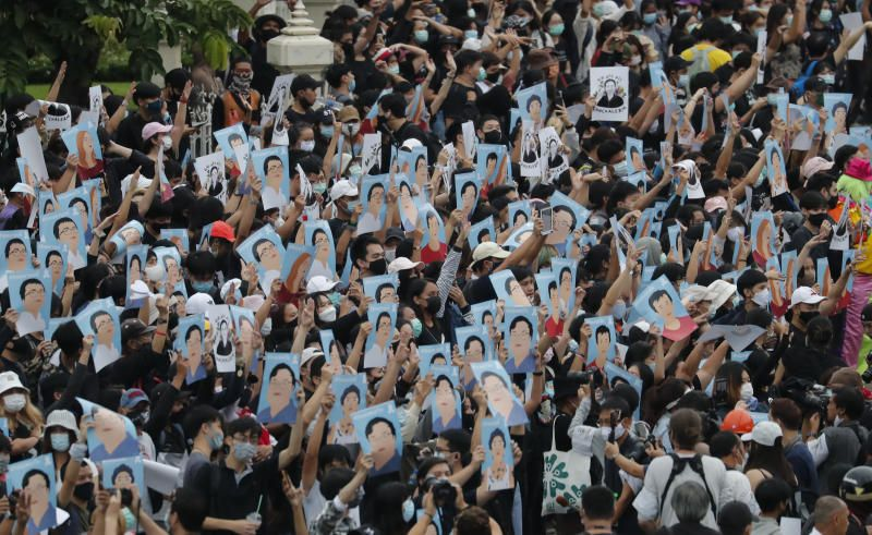 Pro-democracy demonstrators holding posters of protest leaders who have been arrested, during an anti-government protest at Victory Monument in Bangkok, on Sunday (Oct 18, 2020). - AP