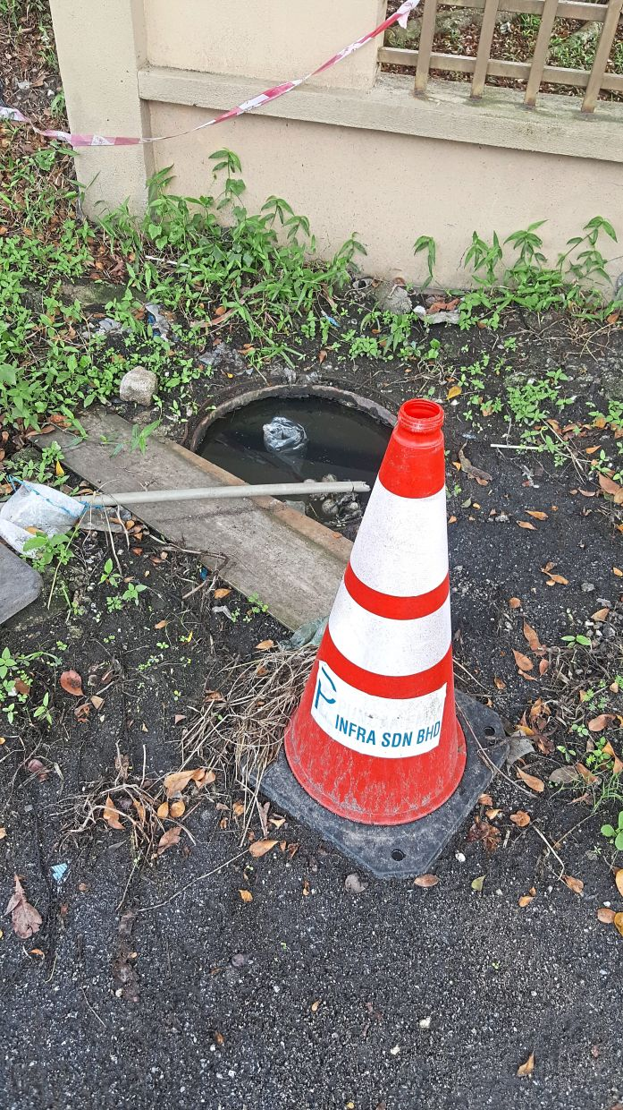 The uncovered manhole near Selarajoo's house is believed to be a breeding ground for mosquitoes.