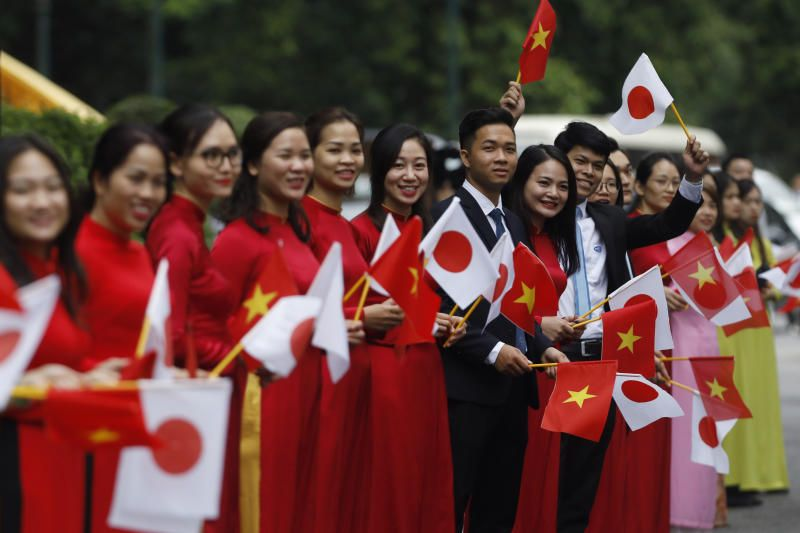 Staff of Vietnam's governent agencies waving Vietnamese and Japanse flags upon arrival of Japanese Prime Minister Yoshihide Suga at the Presidential Palace in Hanoi on Monday (Oct 19). - AP