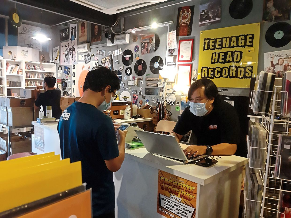Mohd Radzi Jasni (right), the owner of Teenage Head Records in Subang Jaya, will keep his store open daily during the conditional movement control order, while also concentrating on online orders. Photo: Ann Marie Chandy