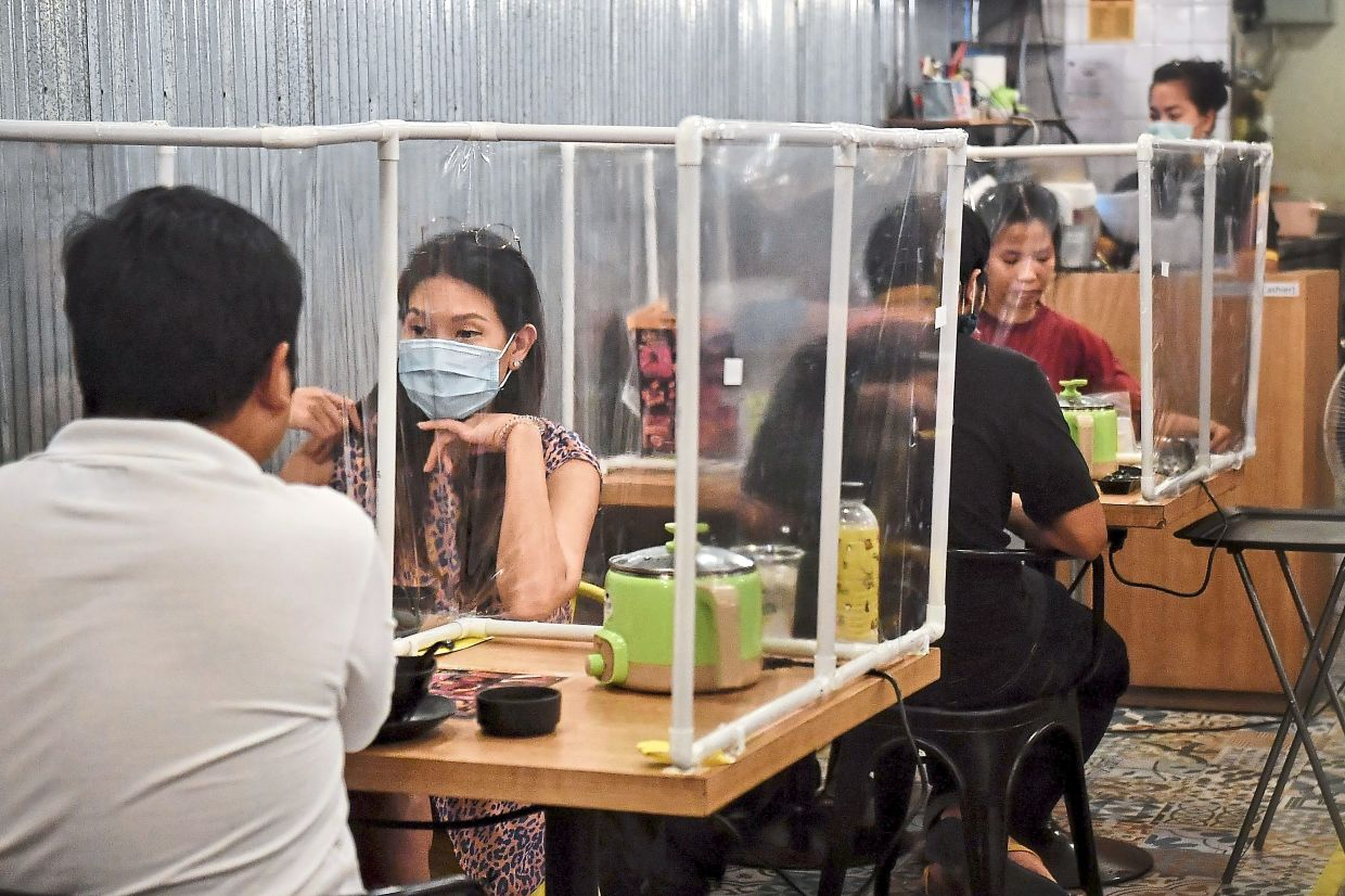 Only two were allowed at a table for dine-in initially during the conditional MCO, although his has been expanded to a maximum of four for bigger tables (five in Selangor). — AFP
