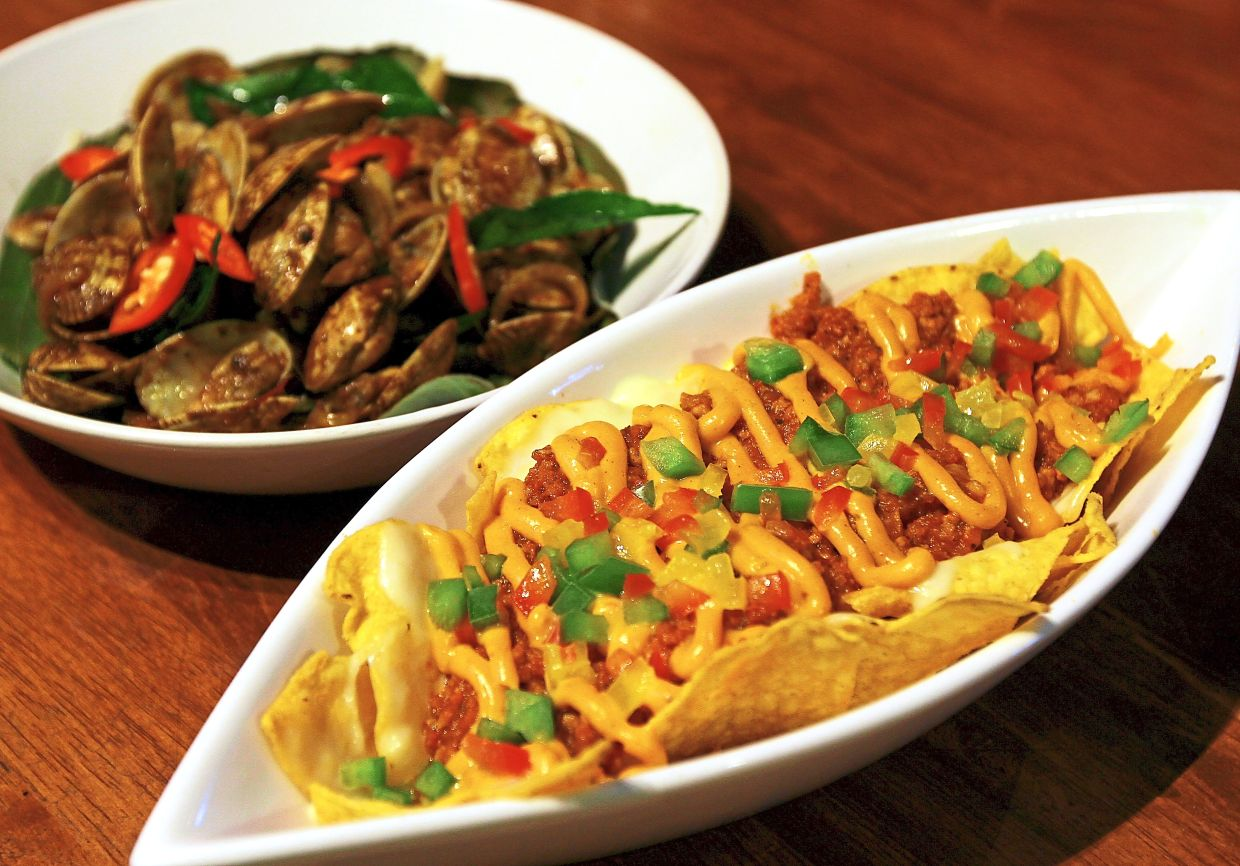Two of Fatboi's signature dishes — Chili Pork Nachos (front) and Kam Heong Lala.