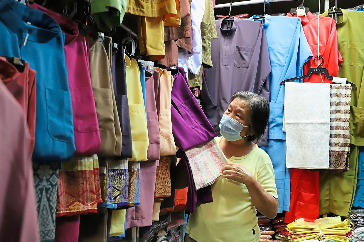 Ooi arranging the tailor-made baju Melayu at her stall which used to enjoy brisk sales during Hari Raya some 10 years ago.