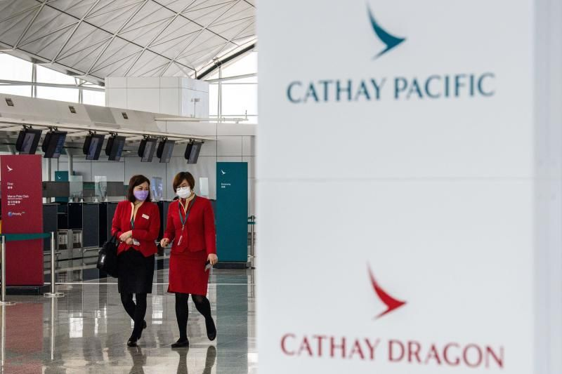 Employees walking past signage for Cathay Pacific and Cathay Dragon near the city's flagship carrier check-in counters at Hong Kong International Airport on Tuesday (Oct 20, 2020). - AFP