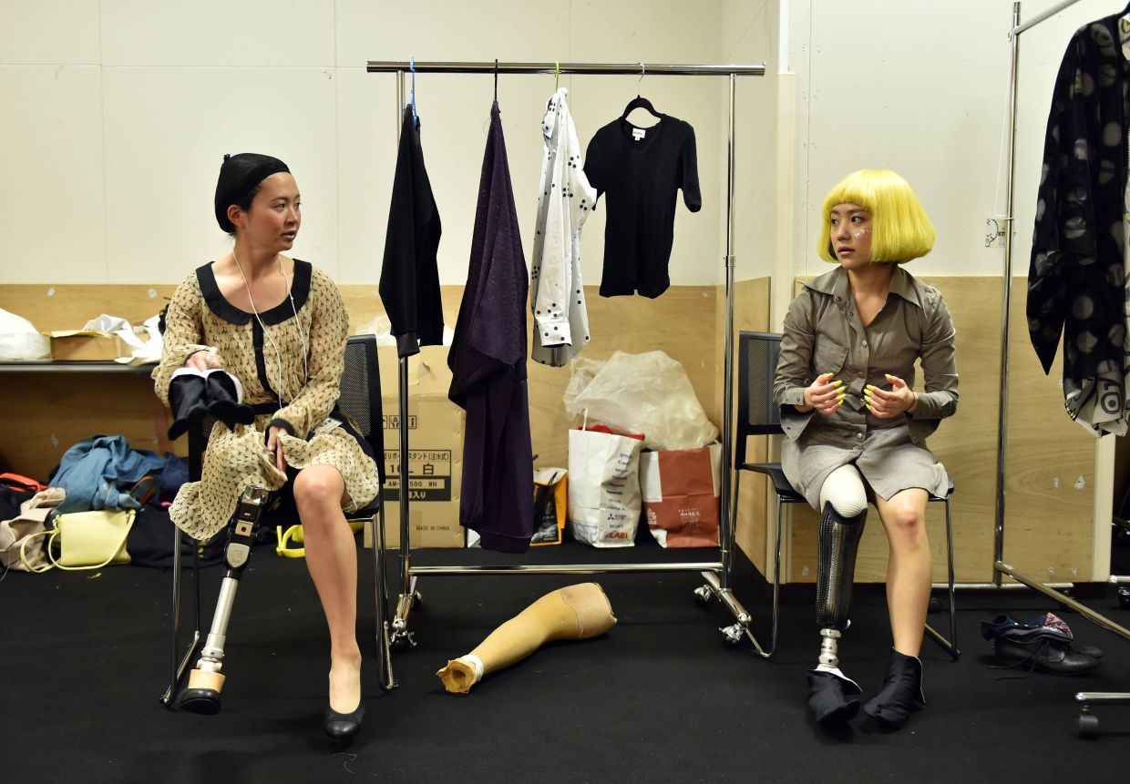 Paralympic athlete Murakami (left) and Paralympic snowboarder Mika Abe chat as they wait backstage to take part in a fashion show for the