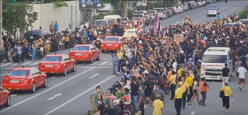 The royal motorcade carrying Thailand's Queen Suthida and Prince Dipangkorn drives past a group of anti-government demonstrators in front of Government House, on the 47th anniversary of the 1973 student uprising, in Bangkok, Thailand October 14, 2020, in this still image obtained from a social media video. Footage taken October 14, 2020.  Reuters