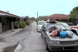 Heaps of rubbish dumped on cars double-parked by mechanic