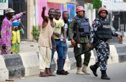 Burned-out buildings and armed gangs in Lagos despite president's plea