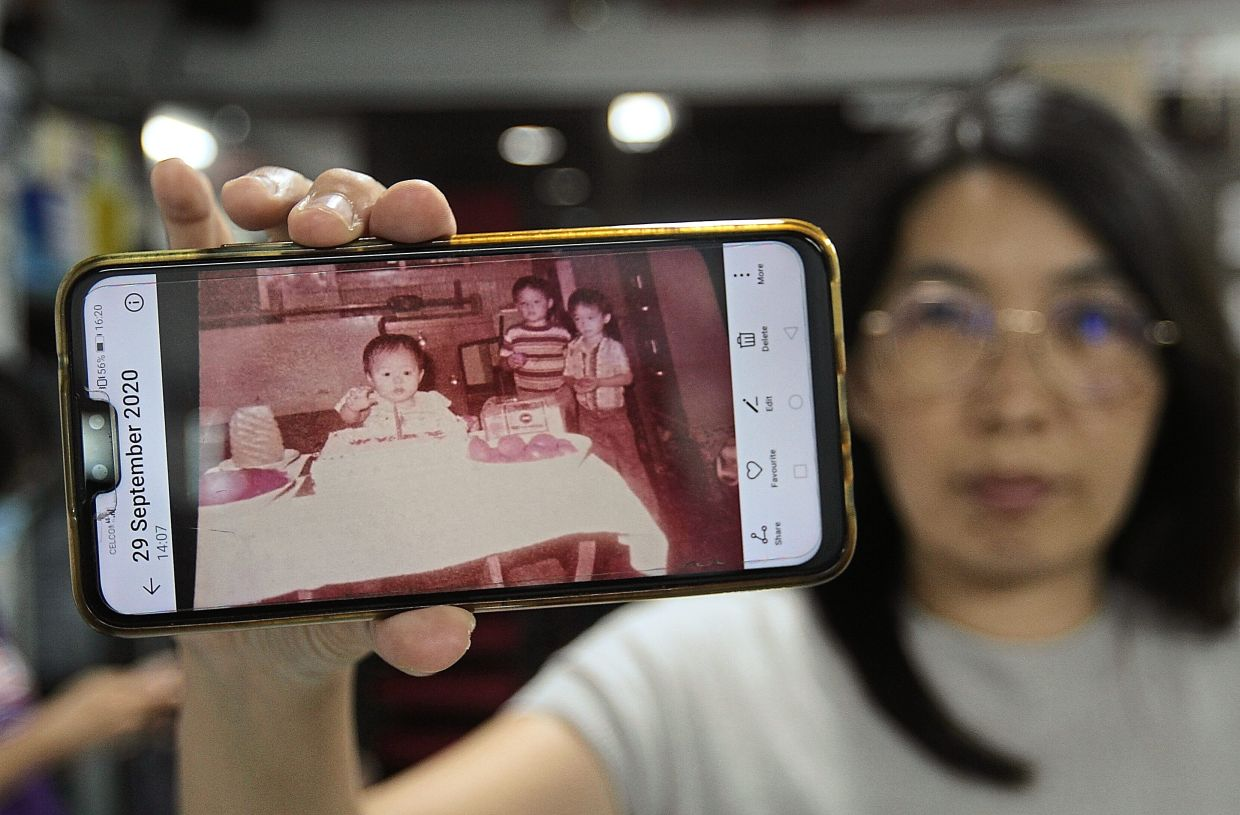 Chong showing an old photo of a family living in Sia Boey during the press conference to announce the project to compile the people's stories.