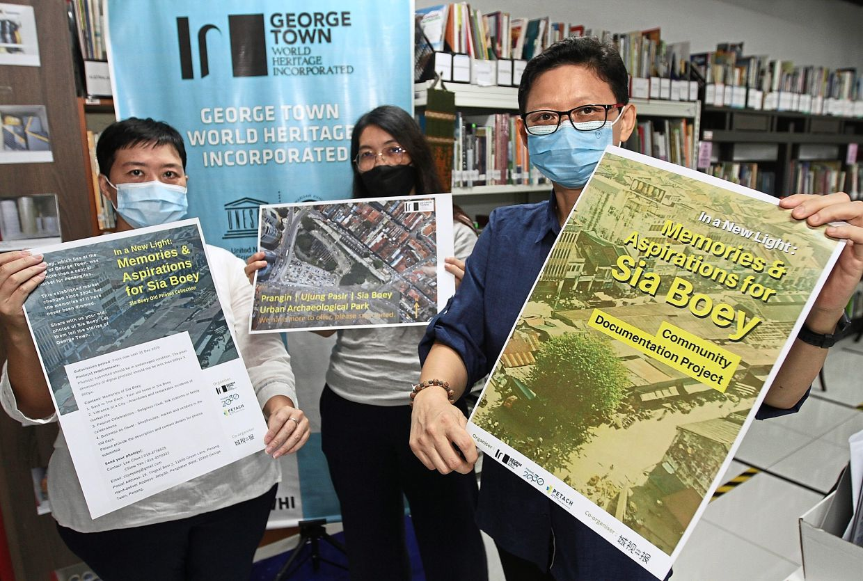 Dr Ang (right) showing the poster on the community documentation project about life in Sia Boey in the good old days.