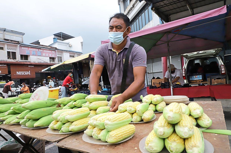 Muhammad Faisol operating his corn stall at the Taman Selamat market.