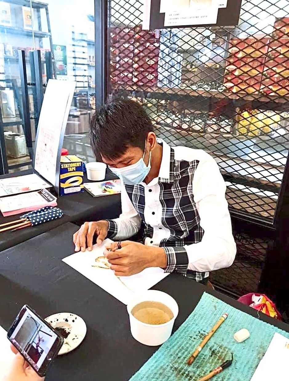 Ai working on a coffee painting during his recent solo exhibition in Kluang.