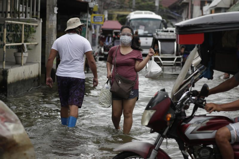 A woman wearing masks to prevent the spread of the coronavirus wades along a flooded road due to Typhoon Molave in Pampanga province, northern Philippines on Monday (Oct 26). A fast moving typhoon has forced thousands of villagers to flee to safety in provinces. - AP