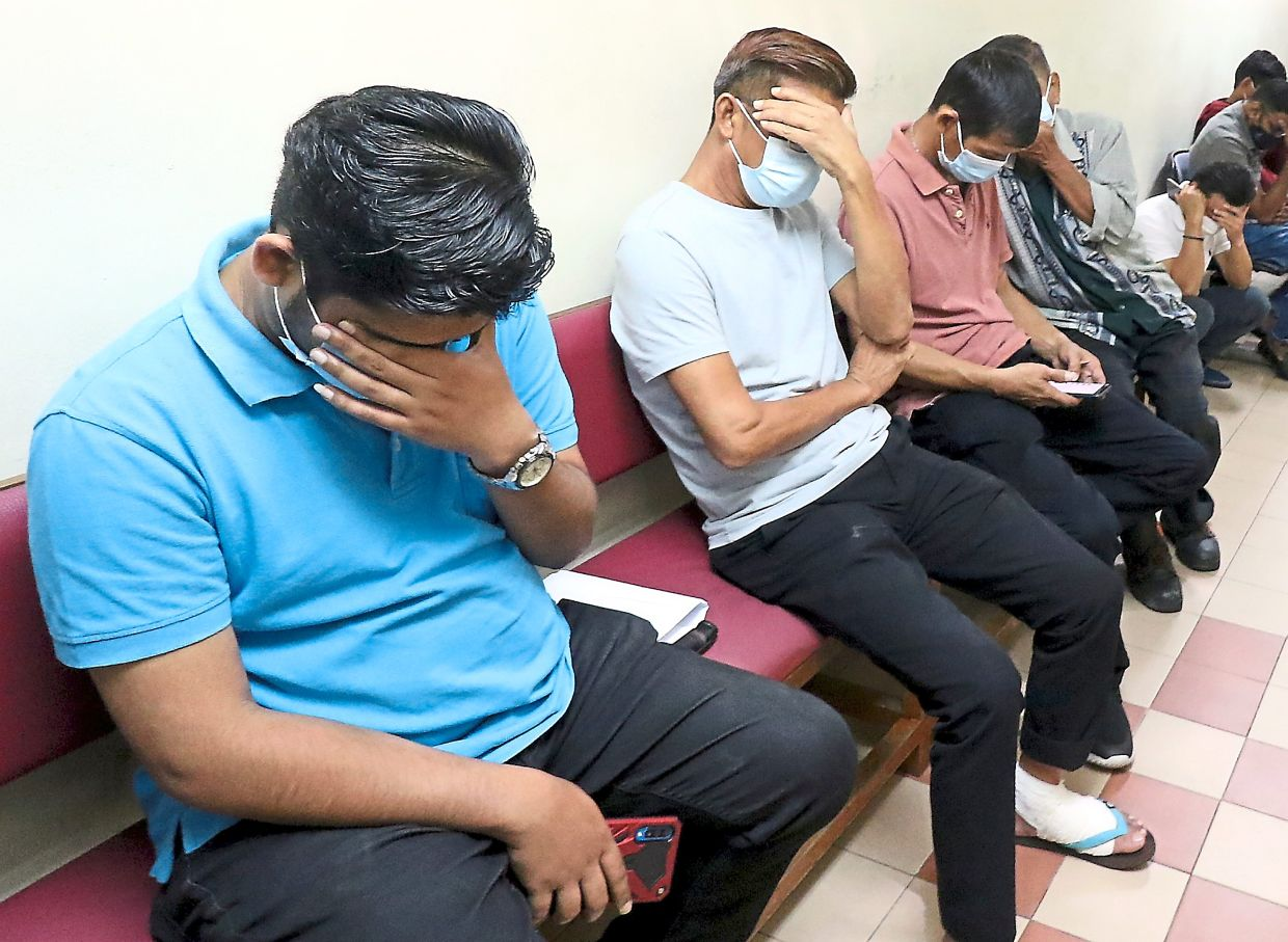 Sitting and waiting: Some of the accused hiding their faces after arriving at the Magistrate's Court in Johor Baru.