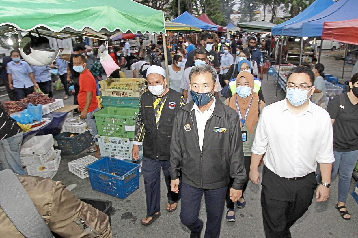 Yew (centre) visiting the Bayan Baru night market to check on SOP  compliance.
