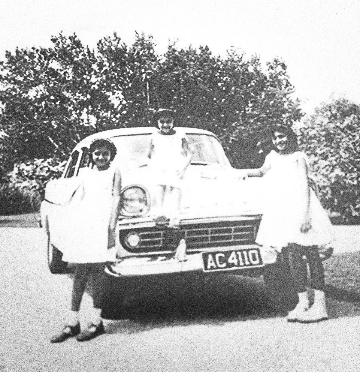 The writer's sisters in their matching dresses, posing with the family Holden. — Rafique Sher Mohamed