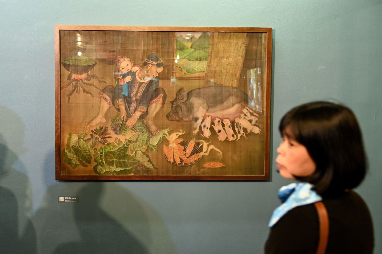 A visitor looking at a painting by Mong Bich during the opening of her first solo exhibition at the French Cultural Centre in Hanoi. Photo: AFP