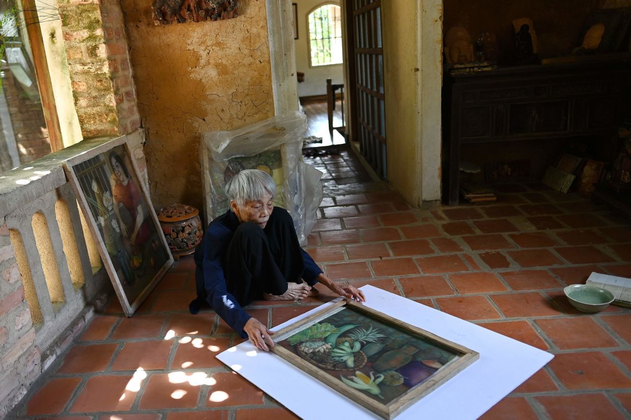 Mong Bich holding a painting inside her house in Bac Ninh province, east of Hanoi. Photo: AFP