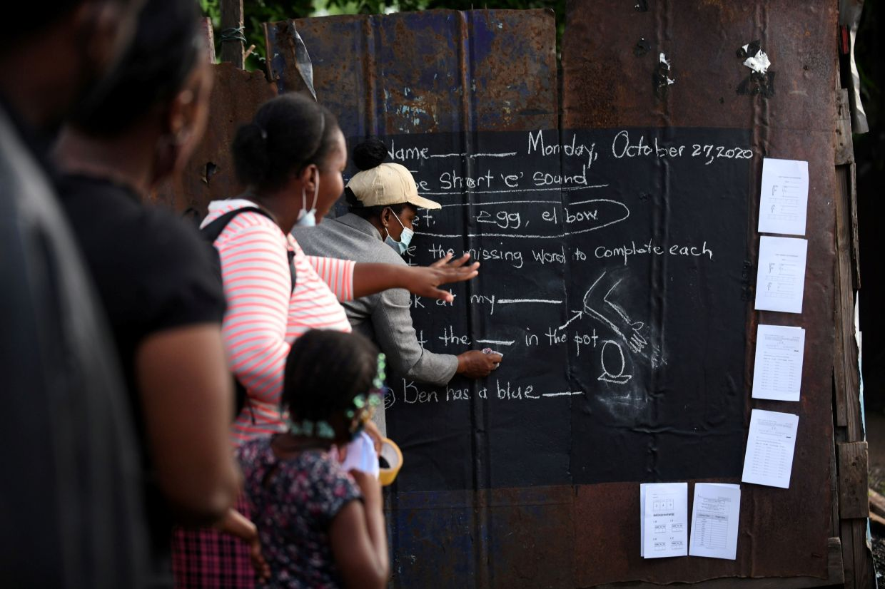 Parents and children of primary school age take photos on their phones of the lessons or write them down in a notebook.