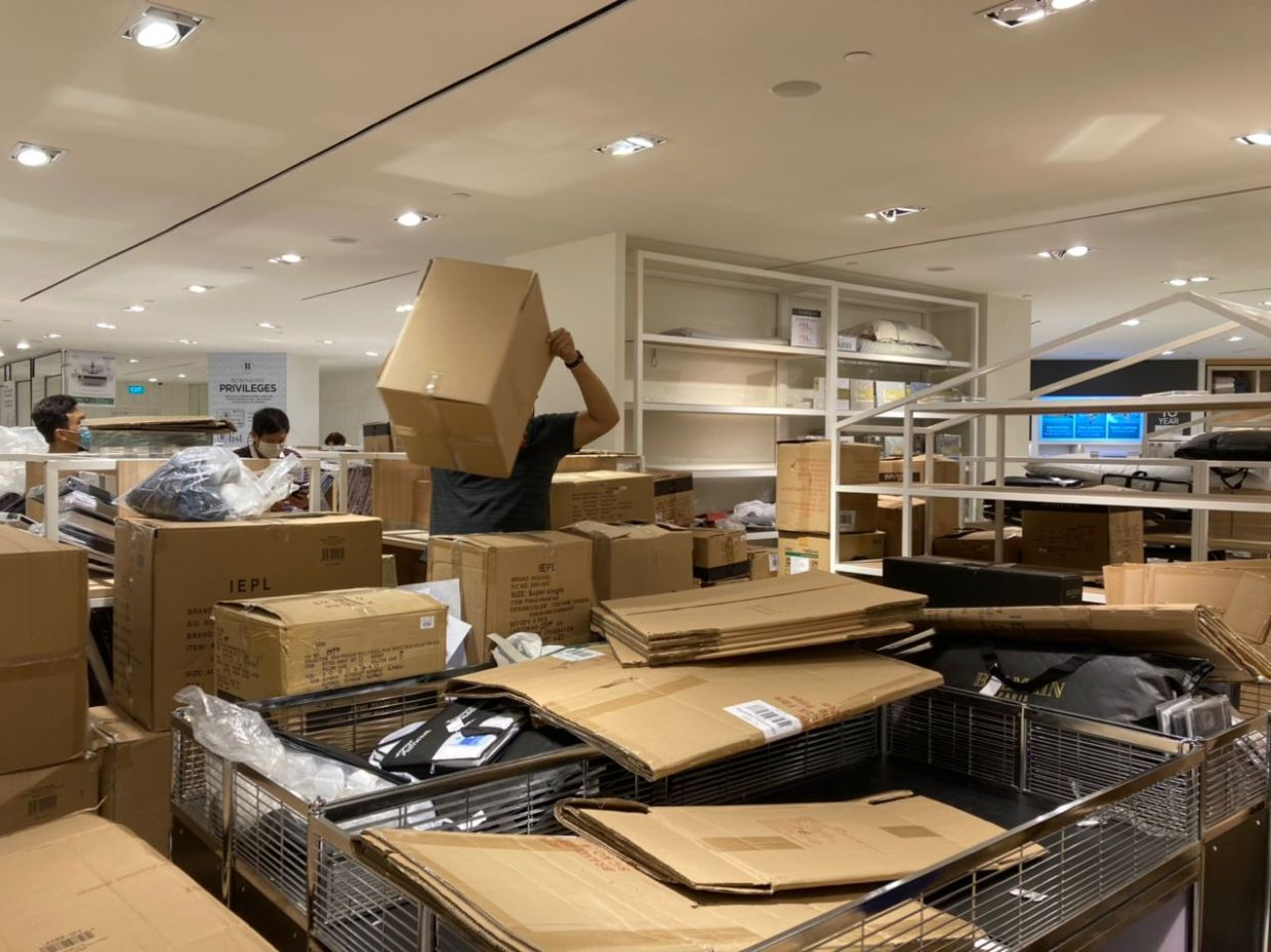 Workers at the Robinsons store in Raffles City packing items from shelves into carton boxes on Friday (Oct 30, 3030). - The Straits Times/Asian News Network