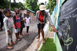 Jamaican teacher turns Kingston walls into blackboards