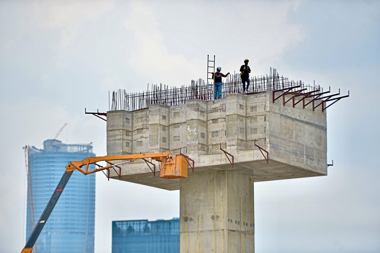 Survival factor: People working at a construction site in Kuala Lumpur. The current third wave of Covid-19 infections had amplified uncertainties in the labour market.