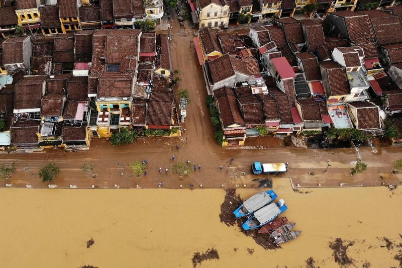 This aerial photograph shows municipal workers cleaning up the streets after flood waters receded in the old city of Hoi An, a UNESCO world heritage site in the aftermath of Typhoon Molave. - AFP