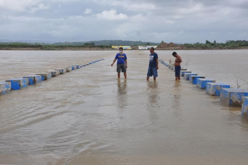 Residents wade in a flooded bridge over a swollen river due to heavy rains in Ilagan town, Isabela province north of Manila on Saturday (Oct 31, 2020) ahead of Typhoon Goni's landfall in the Philippines. - AFP