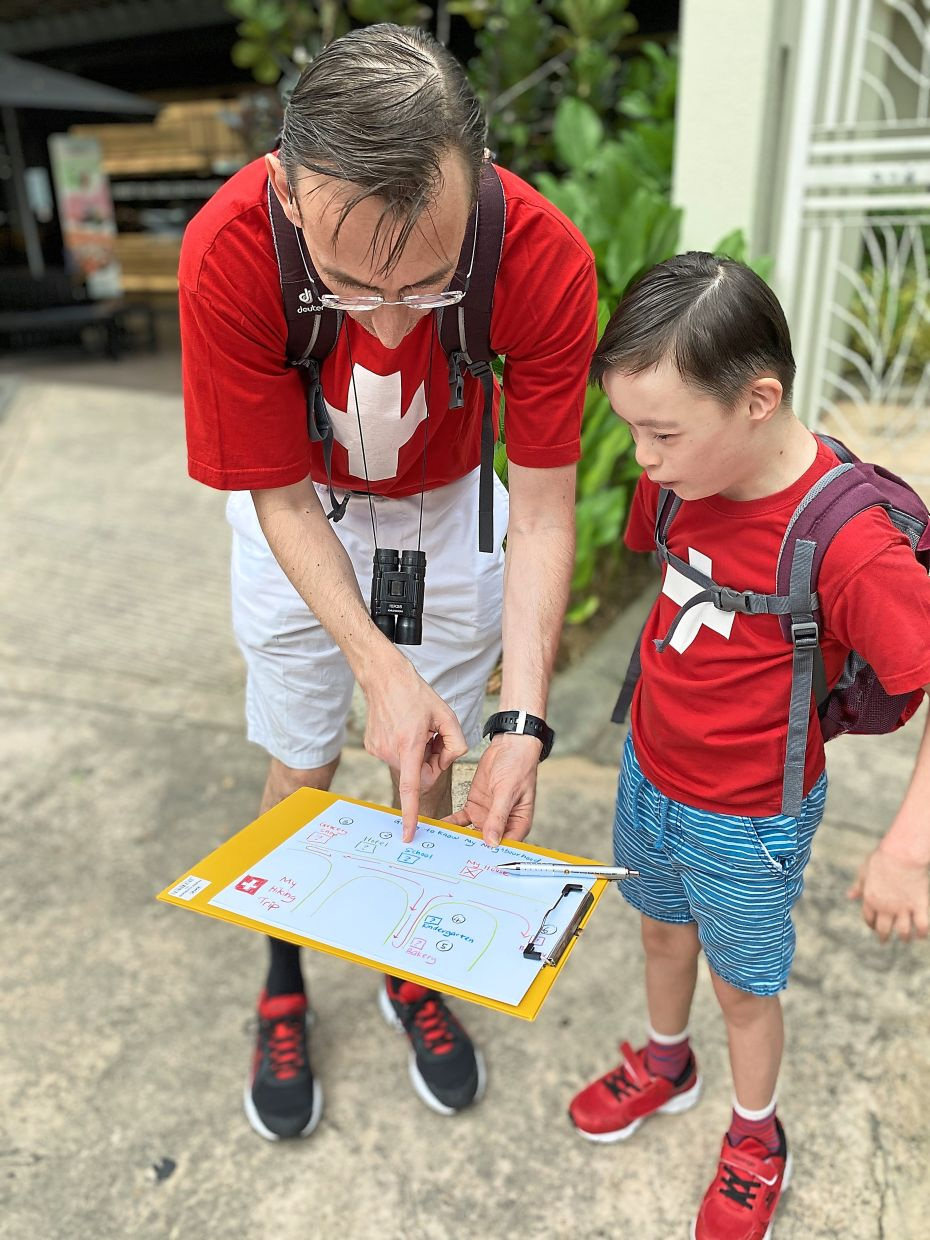 World explorers: Wilhelm (left) teaching Alex how to read a map as part of a make-believe hike in Switzerland.
