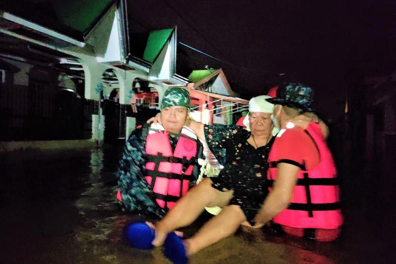 Philippine Coast Guard, rescuers carry a woman following the sudden rise in floodwaters as Typhoon Goni hits Batangas province, south of Manila, Philippines, Sunday, Nov. 1, 2020. The super typhoon blew into the eastern Philippines with disastrous force on Sunday. - AP