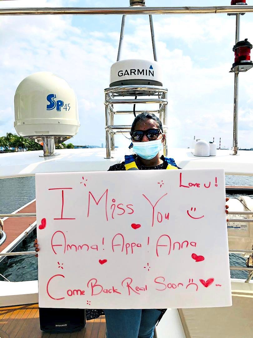 Naavinraj's sister Renaa on the yacht, holds a sign for her parents and brother. Photo: Naavinraj Rengasamy