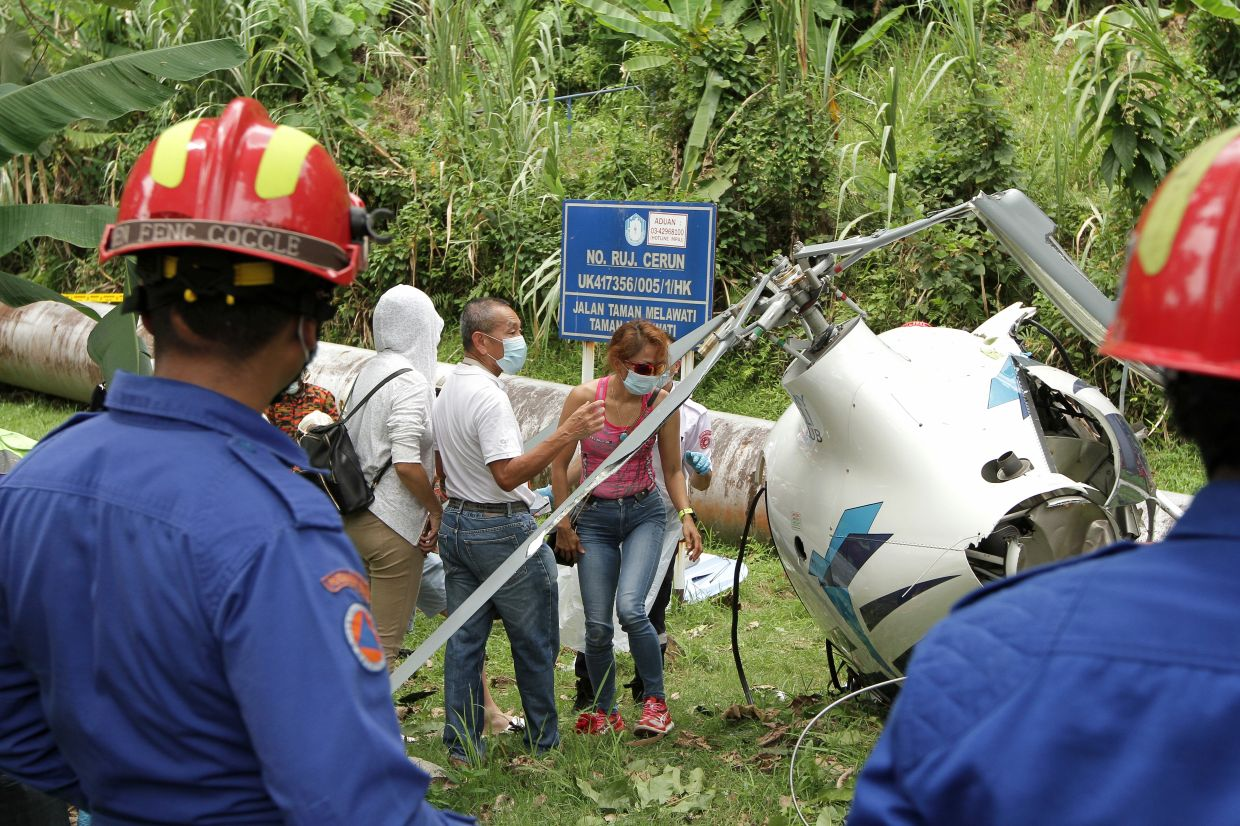 Ex-MAS group chief executive officer Datuk Ahmad Jauhari Yahya and Tan Chai Eian surveying the wreckage of a crashed helicopter that they collided with mid-air in Taman Melawati, Selangor. The two, who are members of the MY Heli Club, survived the collision after safely landing near a school while the other two occupants of the second aircraft were killed in the incident. YAP CHEE HONG/The Star