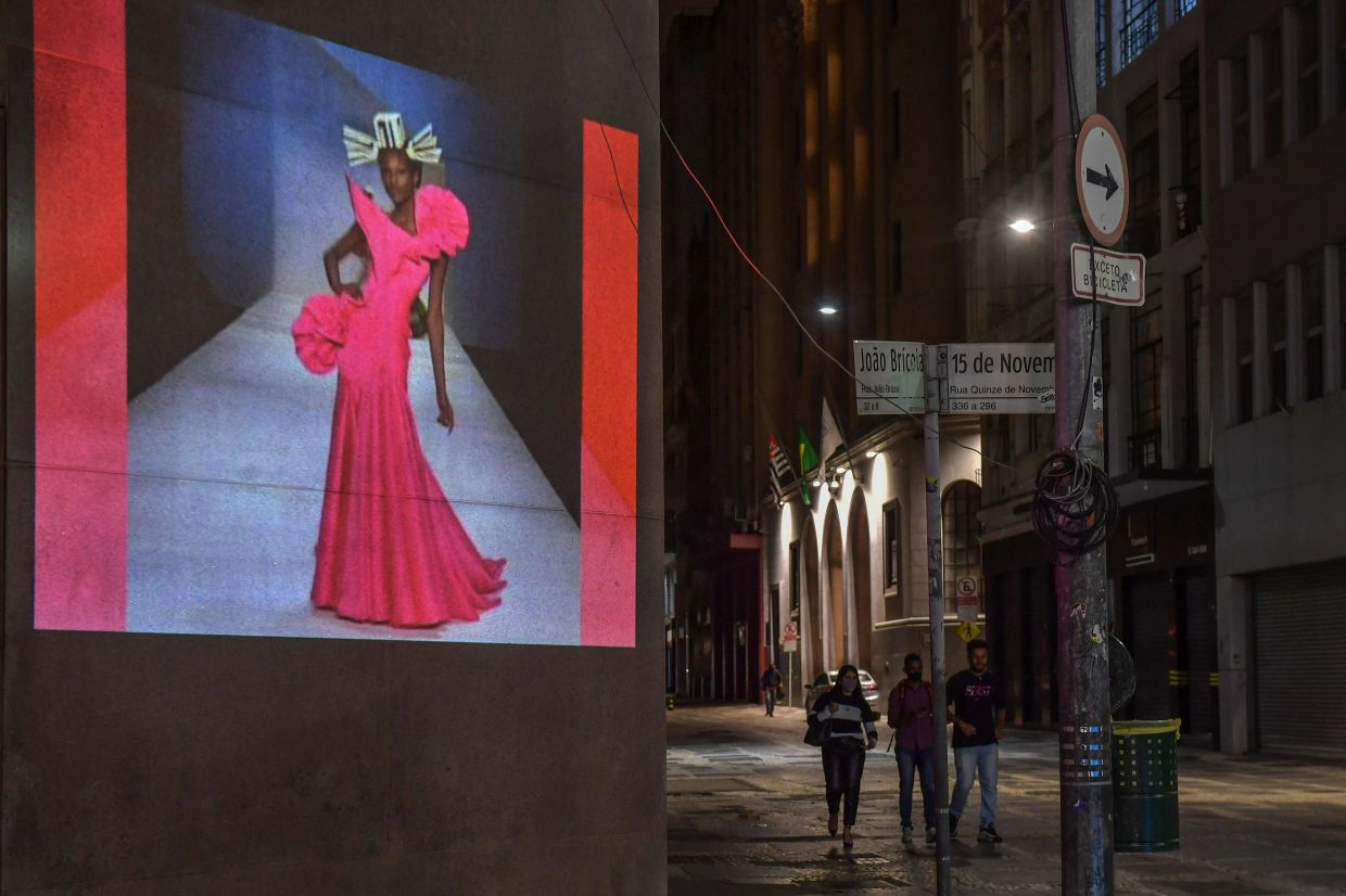 View of an image of a model projected on a building during the first day of Sao Paulo Fashion Week. Photo: AFP